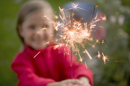 sparkler: Small girl holding sparklers in garden LANG_EVOIMAGES