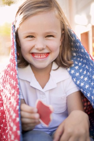 eating area: Small girl with partly-eaten cookie and red teeth (USA) LANG_EVOIMAGES