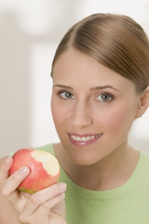 25 to 30 year olds: Woman holding a red apple with bites taken
