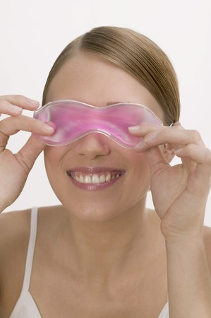 25 to 30 year olds: Woman with a cooling eye mask LANG_EVOIMAGES