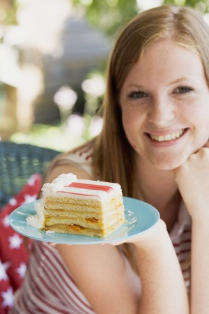 18 25 year old: Woman holding a piece of cake on the 4th of July (USA)