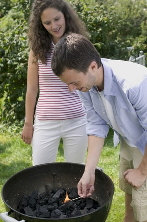 ignited: Couple having barbecue in garden (man lighting charcoal) LANG_EVOIMAGES
