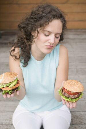 20 to 25 year olds: Woman unable to decide between two different burgers LANG_EVOIMAGES