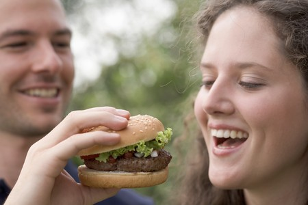 25 to 30 year olds: Man offering woman a bite of hamburger