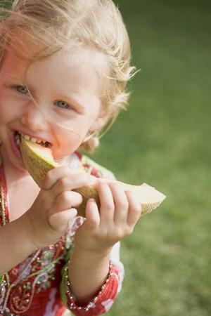 poco: Pequeña muchacha que come una rebanada de melón LANG_EVOIMAGES