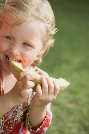 eating area: Small girl eating a slice of melon LANG_EVOIMAGES