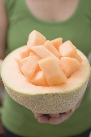 well beings: Woman holding diced melon in hollowed-out cantaloupe melon LANG_EVOIMAGES