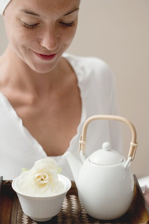 25 to 30 year olds: Woman holding tray with tea and white flower LANG_EVOIMAGES