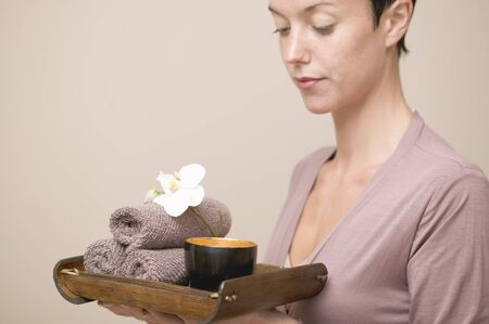 well beings: Woman holding bowl of water, orchid and towels on tray