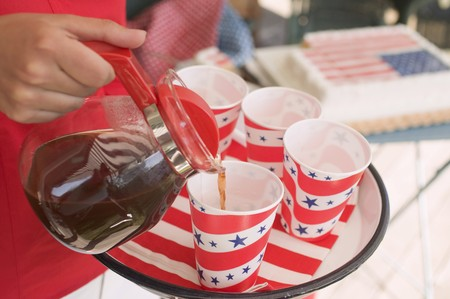 coffeepots: Woman pouring coffee into a paper cup (4th of July, USA)