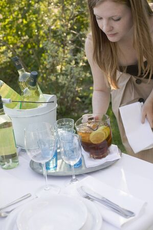 laid back: Woman putting a jug of iced tea on table laid in garden LANG_EVOIMAGES