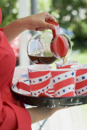 coffeepots: Woman pouring coffee into paper cup (4th of July, USA)