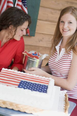 18 25 year old: Two women with cookies and cake on the 4th of July (USA)