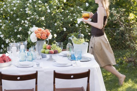 laid back: Woman bringing iced tea to table laid in garden