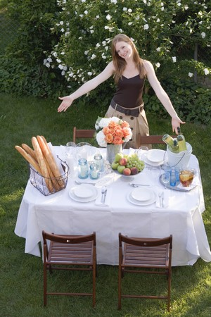 18 25 year old: Woman presenting table laid in garden