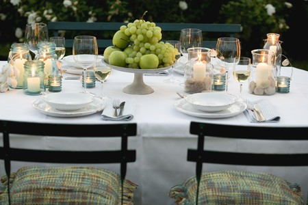 laid back: Bowl of fruit and windlights on table laid in garden