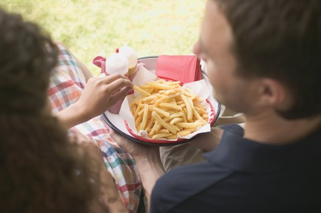 25 to 30 year olds: Couple eating chips in garden