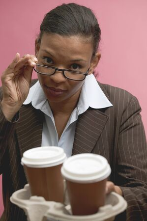 20 to 25 year olds: Businesswoman offering two cups of coffee