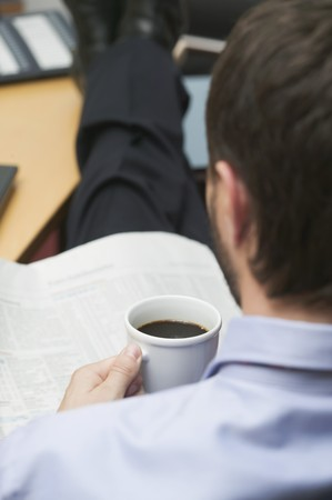 25 to 30 year olds: Businessman drinking coffee while reading newspaper in office