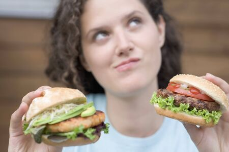 well beings: Woman with two different burgers