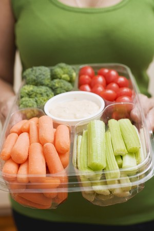crudite: Woman holding plastic tray of vegetables and dip