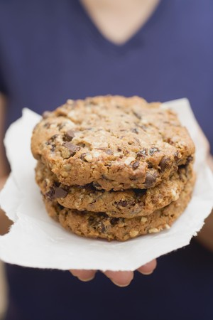 choco chips: Woman holding large chocolate chip cookies on paper LANG_EVOIMAGES