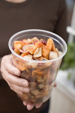 well beings: Woman holding vegetable dish in plastic tub