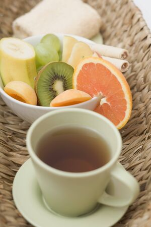 spoiling: Cup of tea, fresh fruit and towel in basket