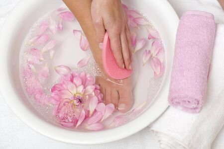 well beings: Woman washing her foot with pink sponge LANG_EVOIMAGES