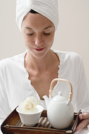 well beings: Woman holding tray with tea and white flower LANG_EVOIMAGES