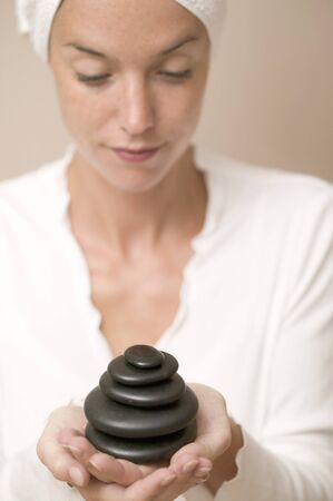 lastone therapy: Woman holding stones for LaStone therapy LANG_EVOIMAGES