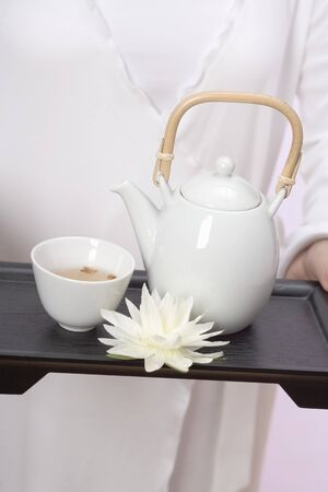 nymphaea odorata: Woman holding teapot, tea bowl and water lily on tray