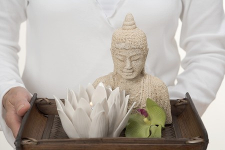 nymphaea odorata: Woman holding Buddha statue, candle and orchid on tray