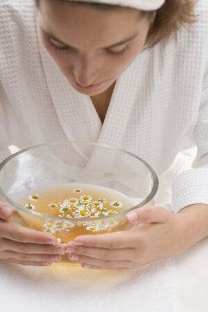 well beings: Woman bending over bowl of chamomile tea with flowers LANG_EVOIMAGES