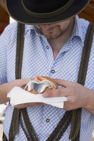 eating area: Man eating herring roll at Oktoberfest