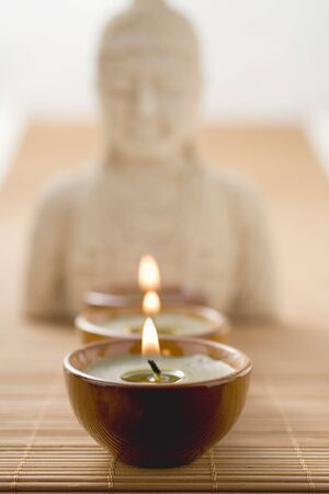Three tea lights on bamboo mat in front of Buddha statue