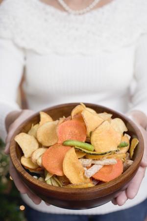 waist deep: Woman holding wooden bowl of vegetable crisps