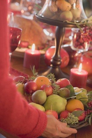 Woman placing bowl of fruit on table laid for Christmas LANG_EVOIMAGES