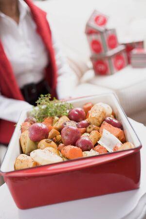 root vegetables: Arrosto di ortaggi a radice nel piatto torrefazione, la donna in background LANG_EVOIMAGES