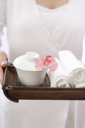 well beings: Woman holding towels, bowl and orchid on tray