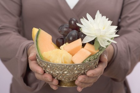 nymphaea odorata: Woman holding bowl of fresh fruit with water lily