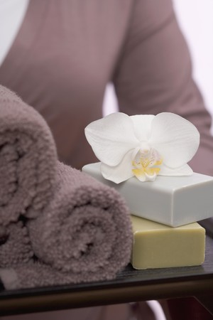 well beings: Woman holding towels, soaps and orchid on tray LANG_EVOIMAGES
