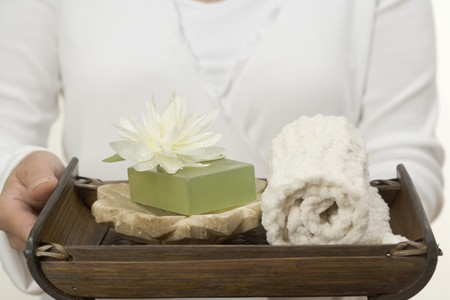 well beings: Woman holding soap, water lily and towel on tray LANG_EVOIMAGES