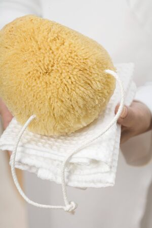 well beings: Hands holding bath sponge on white towel