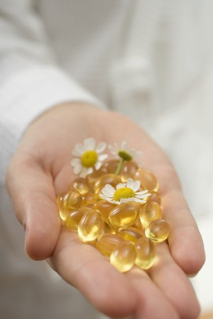 german chamomile: Hand holding vitamin capsules and chamomile flowers LANG_EVOIMAGES