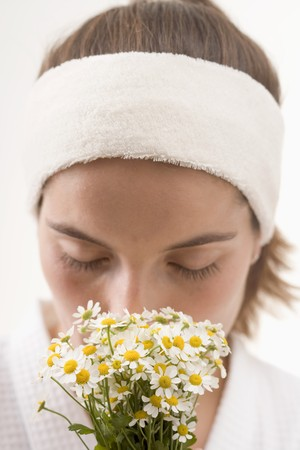german chamomile: Woman smelling chamomile flowers