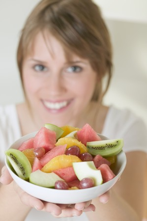 well beings: Woman holding dish of fruit salad LANG_EVOIMAGES
