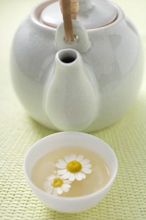 german chamomile: Teapot and bowl of chamomile tea