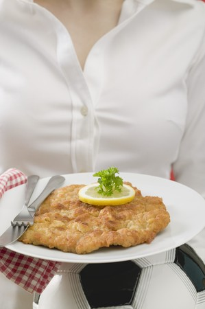 blouses: Woman holding plate of Wiener schnitzel (veal escalope) on football