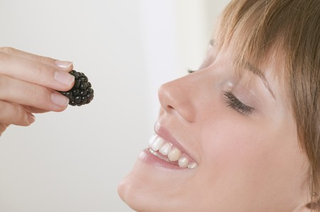 well beings: Woman holding a blackberry up to her mouth
